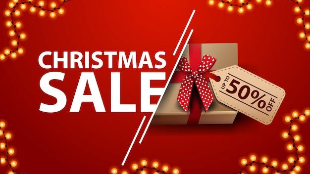 Banner de descuento rojo de venta de navidad con guirnalda y presente con lazo y etiqueta de precio