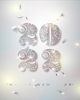 Banner de feliz año nuevo con números de plata 2022 sobre fondo brillante con confeti volador.