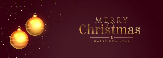 Banner de feliz navidad con balón de oro y destellos