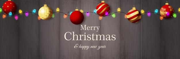 Banner de feliz navidad con bolas rojas sobre suelo de madera gris