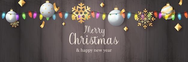 Banner de feliz navidad con bolas en suelo de madera gris
