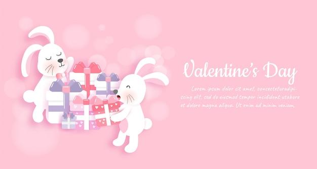 Banner y fondo de san valentín con lindos conejos y cajas de regalo en estilo de corte de papel