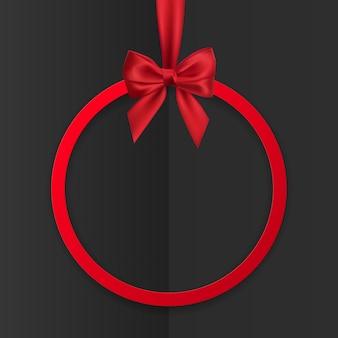 Banner de marco redondo de vacaciones brillante que cuelga con cinta roja y lazo sedoso sobre fondo negro.