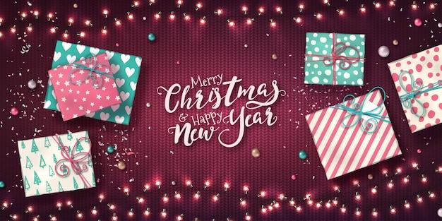 Banner de navidad y año nuevo con cajas de regalo, guirnaldas de luces de navidad,
