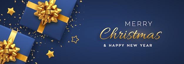 Banner de navidad. cajas de regalo azul realistas con lazo dorado, estrellas doradas y confeti brillante.