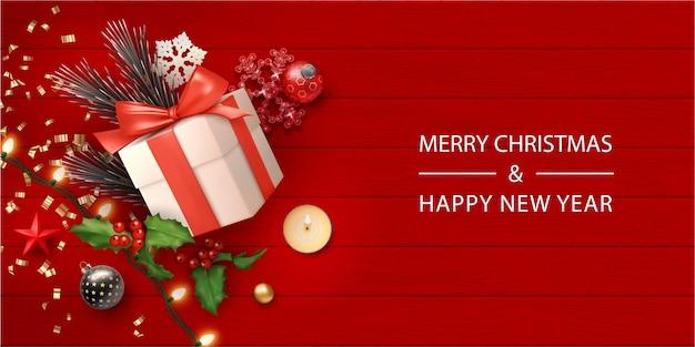 Banner realista de feliz navidad con caja de regalo y adornos navideños