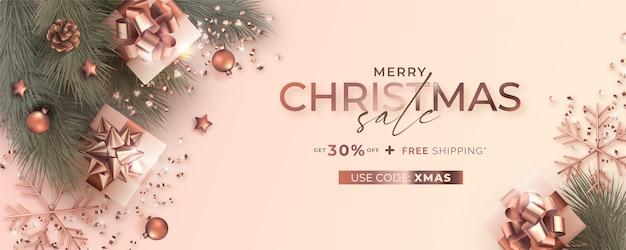 Banner de rebajas navideñas con decoración realista en rosa dorada