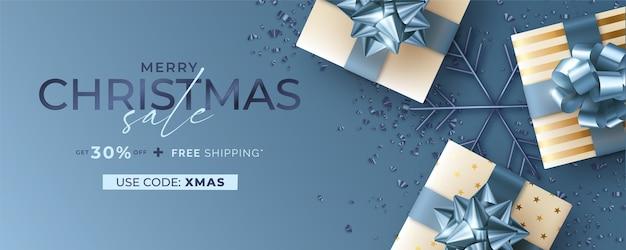 Banner de rebajas navideñas con regalos realistas en azul y dorado.