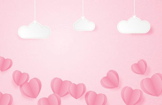 Banner de san valentín con forma de corazón flotando sobre fondo rosa y nubes colgantes en papel cortado estilo.
