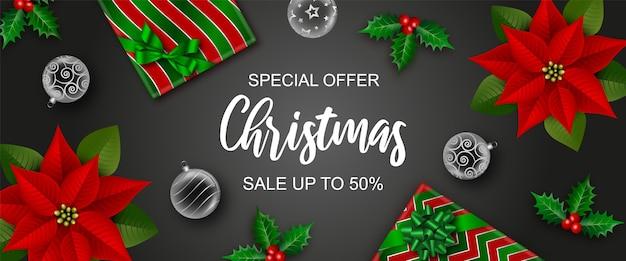Banner de venta de navidad con cajas de regalo, bolas de navidad, flores de acebo y poinsettia