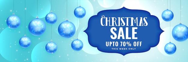 Banner de venta de navidad elegante con bolas azules colgantes
