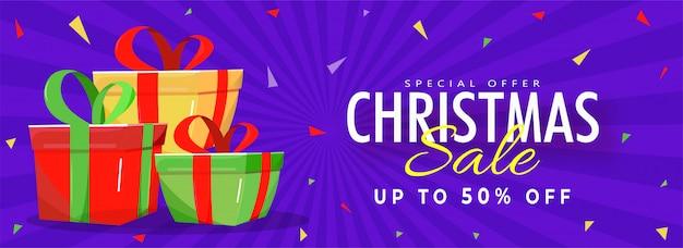 Banner de venta de navidad con oferta de descuento del 50% y cajas de regalo sobre fondo de rayos púrpura.