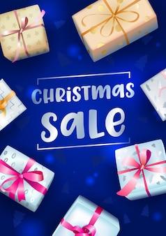 Banner de venta de navidad con tipografía y cajas de regalo festivas envueltas sobre fondo azul borroso