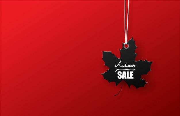 Banner de venta otoño con hoja negra sobre fondo rojo