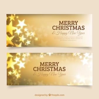 Banners dorados de feliz navidad y año nuevo con estrellas
