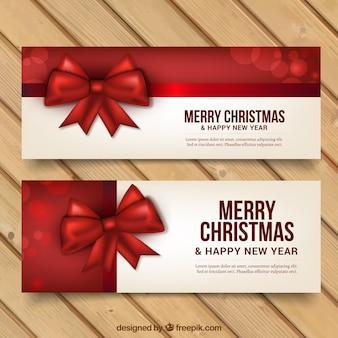 Banners de feliz navidad y año nuevo con lazos rojos