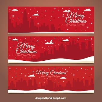 Banners rojos de feliz navidad con silueta de ciudad