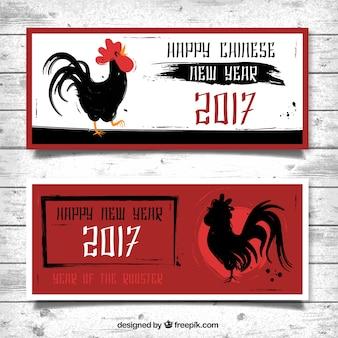Banners rojos con gallos de tinta para el año nuevo chino