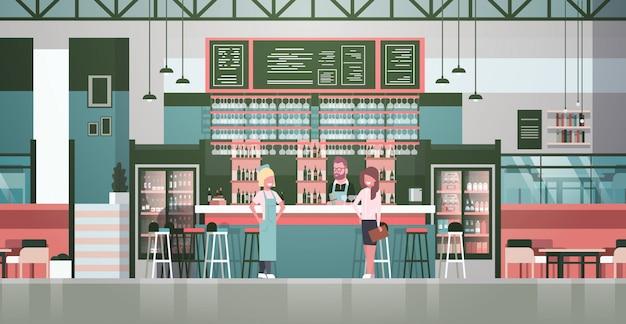 Barman, camarero, camarero y administrador de pie en el mostrador de botellas de alcohol y vasos