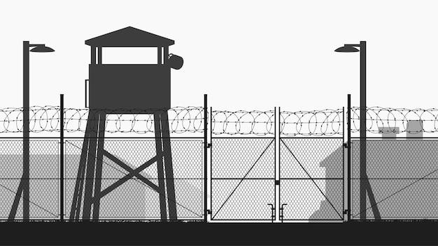 Base militar con torre de guardia y silueta de valla de cadena