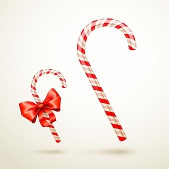 Bastón de caramelo de navidad con lazo rojo aislado sobre fondo blanco.