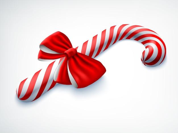 Bastón de caramelo realista decorado con lazo rojo sobre blanco