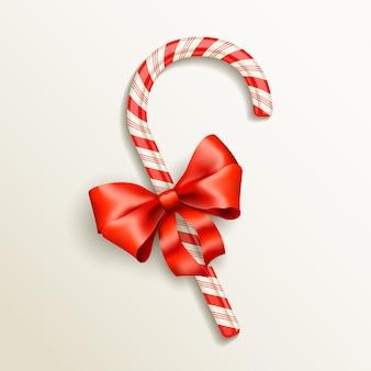Bastón de caramelo realista con ilustración de vector de lazo rojo