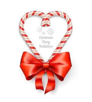 Bastones de caramelo en marco en forma de corazón con texto para invitación de navidad