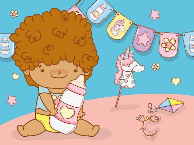Bebé de pelo rizado y biberón.