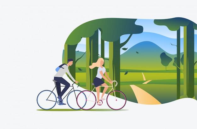 Bicicletas del montar a caballo del hombre y de la mujer con paisaje verde en fondo