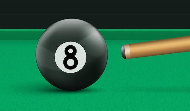 Billar bola ocho y taco sobre mesa de tela verde