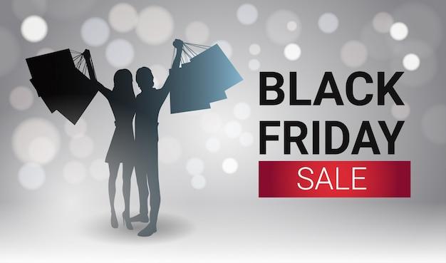 Black friday sale banner design con silueta pareja sosteniendo bolsas de compras sobre luces blancas bokeh