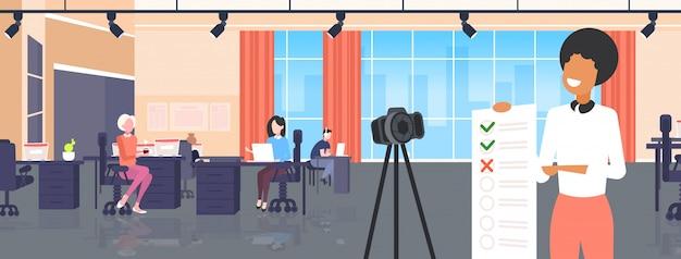 Blogger presentando lista de verificación encuesta formulario de examen mujer grabando video en línea con cámara en trípode evaluación de resultados concepto de blogs moderno oficina interior retrato horizontal