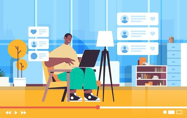Blogger de tecnología grabación online video blog live streaming blogging concepto hombre afroamericano vlogger usando laptop sala interior horizontal