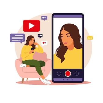 Blogger de video de mujer sentada en el sofá con teléfono y grabación de video con teléfono inteligente. diferentes iconos de redes sociales. en estilo plano.