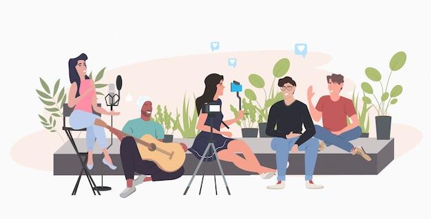 Blogueros que usan el teléfono inteligente de grabación de video blog tocando la guitarra y cantando al micrófono personas que transmiten en vivo el concepto de blog de la red de redes sociales horizontal integral