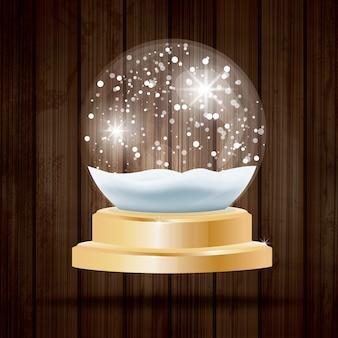 Bola de cristal de navidad con nieve sobre fondo de madera