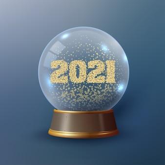 Bola de navidad con los números 2021 en su interior que están formados por purpurina dorada.