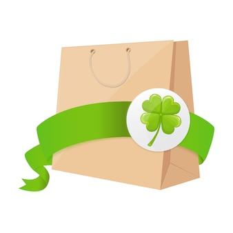 Bolsa de papel con cinta verde y trébol de cuatro hojas.