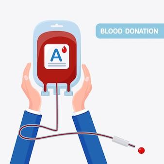 Bolsa de sangre con gota roja en mano aislado en blanco