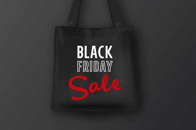 Bolsa de tela negra con la inscripción venta de viernes negro closeup sobre fondo negro
