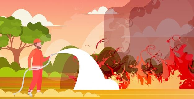 Bombero extinción de incendios forestales peligrosos en australia bombero rociando agua de la manguera de lucha contra incendios incendio contra incendios concepto de desastres naturales intensas llamas naranjas horizontales