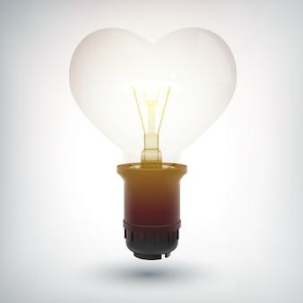 Bombilla incandescente con concepto de base de plástico en forma de corazón como símbolo de amor aislado