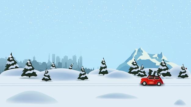 Bosque de pinos de invierno, ciudad de silueta, montaña nevada y coche vintage rojo con árbol de navidad