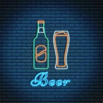 Botella de cerveza y vidrio con letras en estilo neón en pared de ladrillo