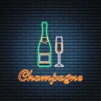 Botella de champán y vidrio sobre fondo de ladrillo.