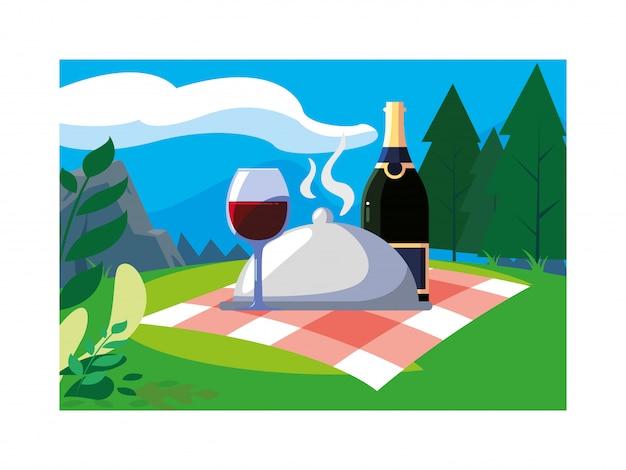 Botella y copa de vino con paisaje de fondo