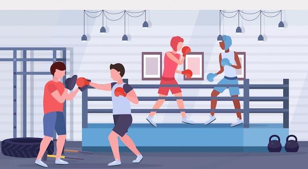 Boxeadores ejercicio kick boxing mix luchadores de raza en guantes y cascos protectores practicando juntos lucha club ring arena interior estilo de vida saludable concepto plano horizontal