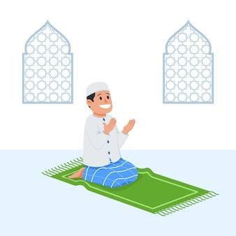 Boy musulmán sentarse y rezar en estera de oración
