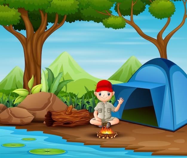 Boy scout sentado en el camping